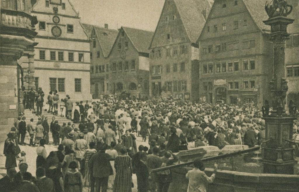"""Touristen bevölkern den Marktplatz, um der """"Meistertrunk""""-Spieluhr zuzusehen (Bild 1932)"""
