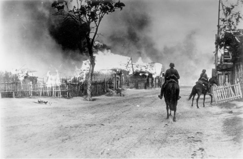 Deutsche Kavalerie und ein brennendes Dorf